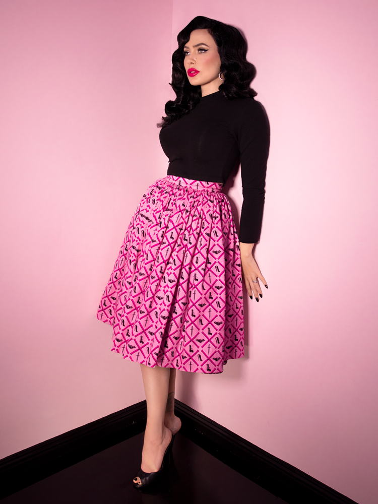 Full length shot of Micheline Pitt standing against a pink wall wearing a black long sleeve vintage inspired top and pink knee length skirt with design print.
