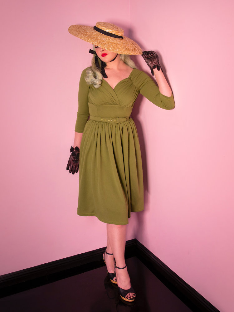 A vintage inspired dress worn by model also wearing black lace gloves and a naturally colored sunhat.