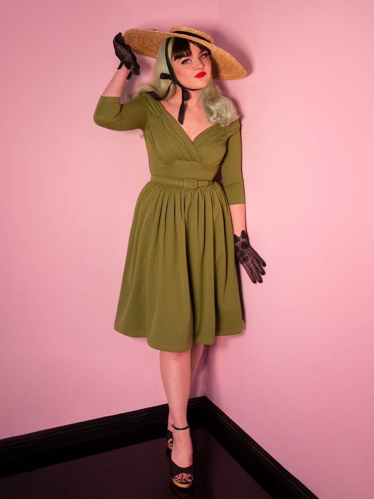 Green vintage dress being worn by model also wearing a natural sunhat.