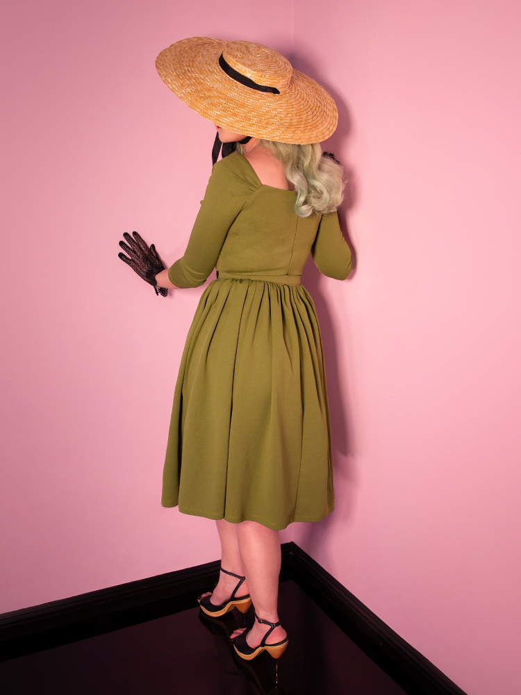 Backshot of mdoel in moss green dress.