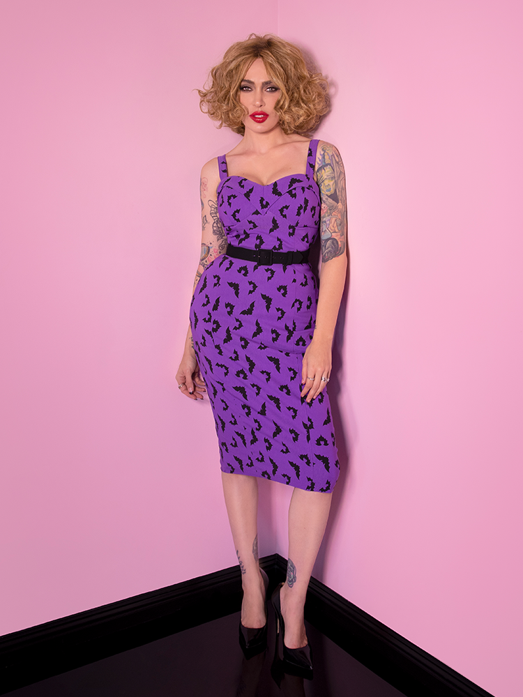 Wearing a purple retro style dress, Micheline stares intently into the camera.