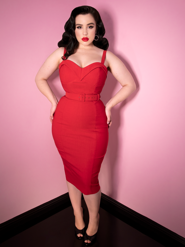 A black haired model wearing the Maneater Wiggle Dress in Red from Vixen Clothing.