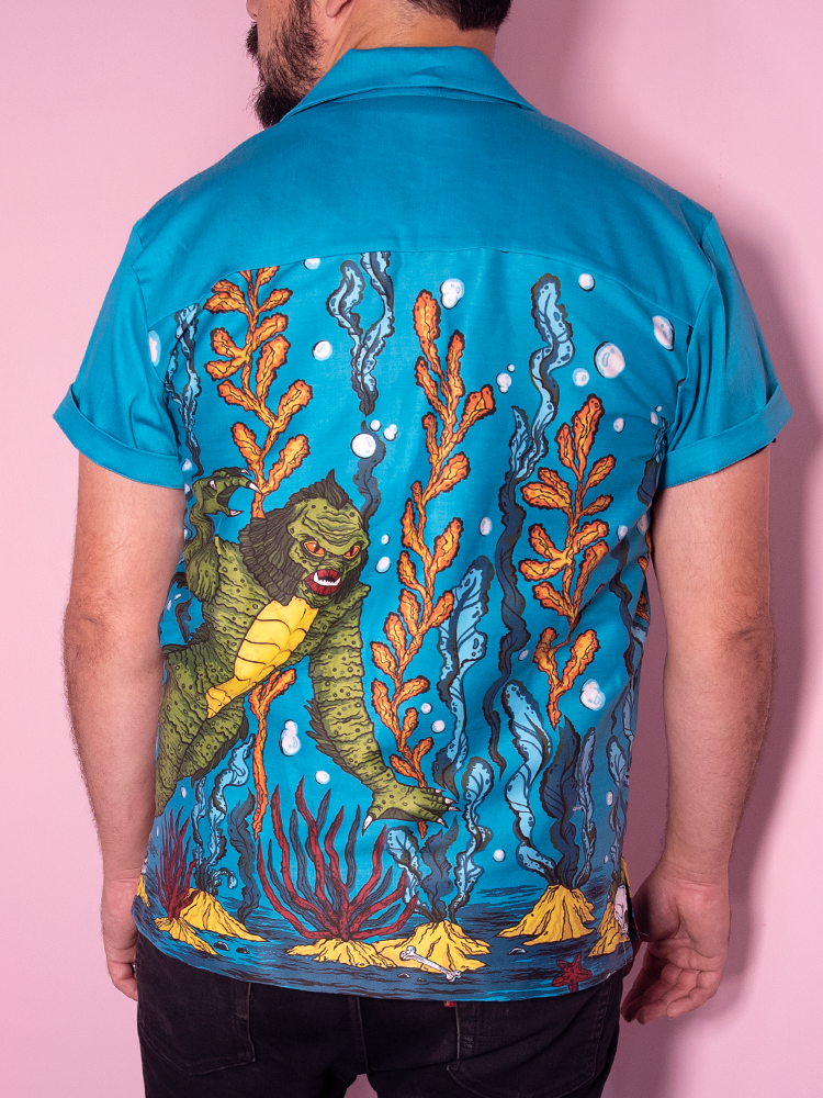 Back view of male model wearing the creature retro shirt from Vixen Clothing. It features an ocean scene with a swamp creature swimming.