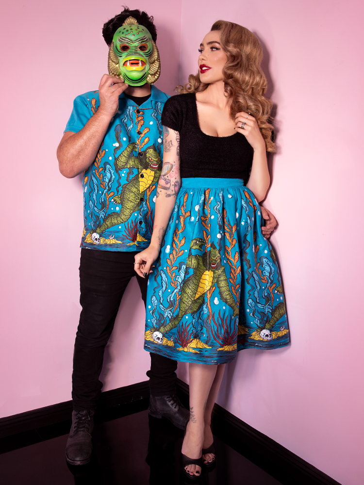 Male model covering his face with a swamp creature masks, wears the Men's Button Up in Swamp Monster Print from Vixen Clothing. Also joining him in the shot is Micheline Pitt, model and owner, who is wearing her own sea creature skirt and black retro top.