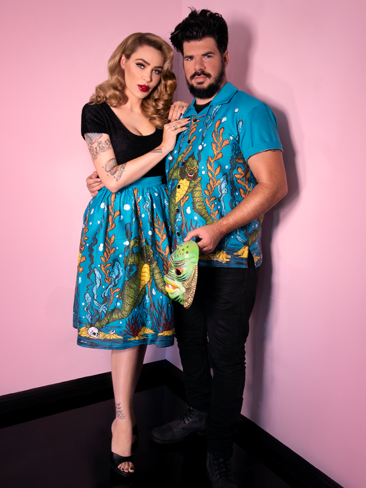 Male model and Micheline Pitt posing together wearing matching swamp monster print outfits.