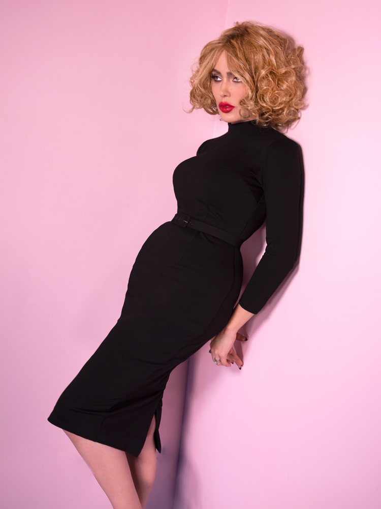 Micheline Pitt leaning against a pink wall wearing the Bad Girl Wiggle Dress in Black.