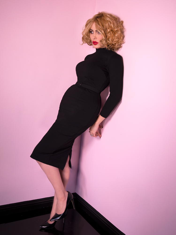 Full length shot of Micheline Pitt wearing the Bad Girl Wiggle Dress in Black with black shiny heels.