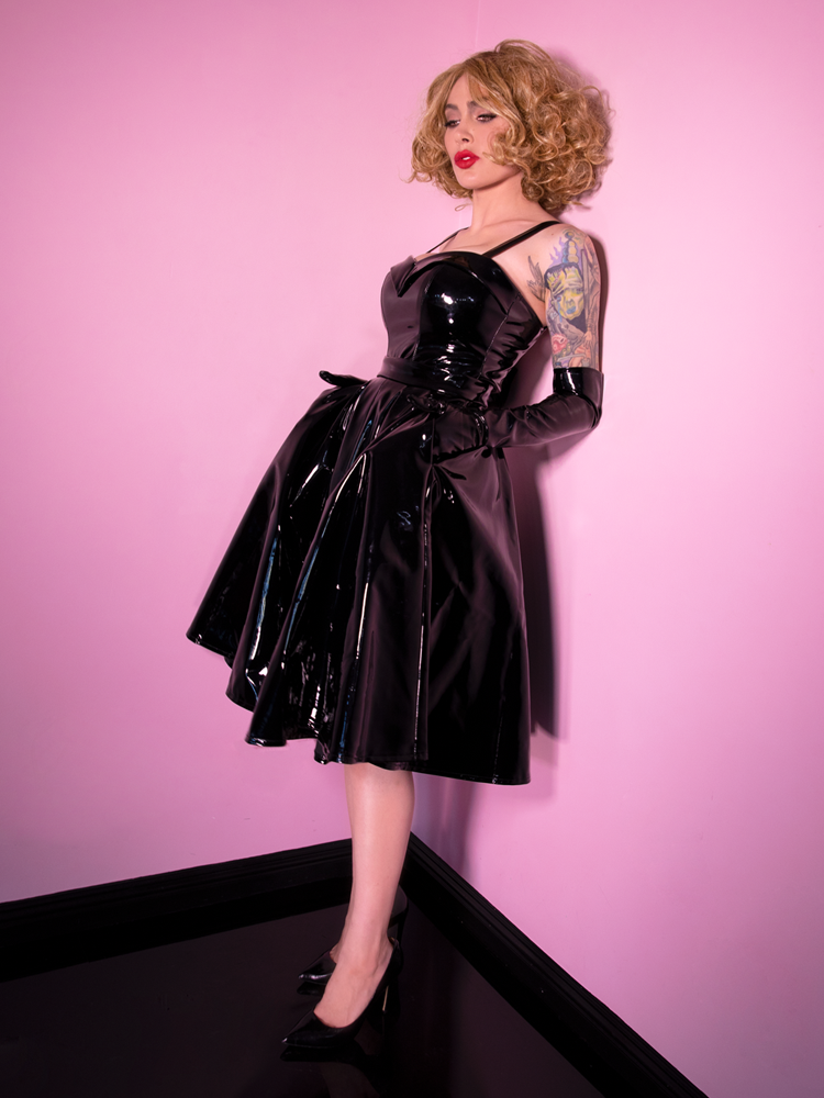 Full length shot of Micheline Pitt wearing a vintage inspired outfit - black latex skirt, thin strap black latex top and black shoes.