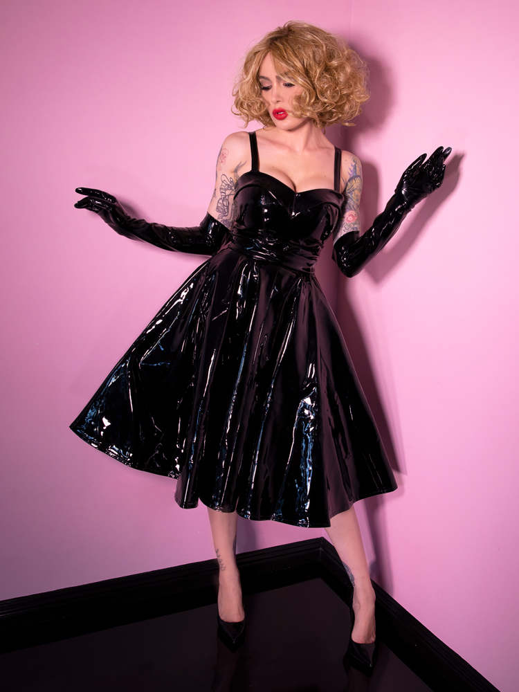 Micheline Pitt, Vixen Clothing owner and model, caught striking a pose in elbow length black latex gloves, top of the same color and fabric and the Miss Kitty Circle Skirt in Black Vinyl.