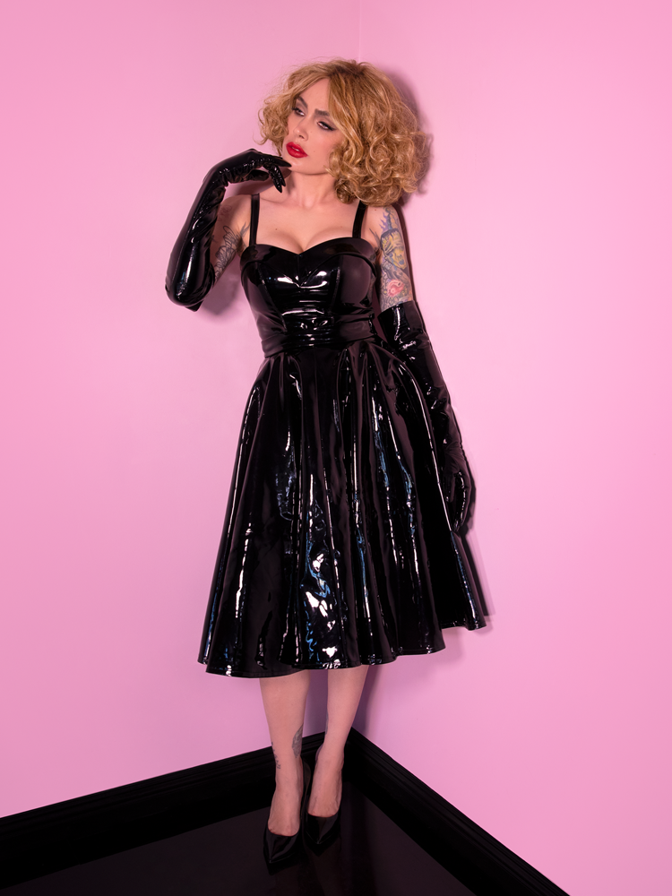 Caught in a look of wonderment, Micheline Pitt models the Miss Kitty Circle Skirt in Black Vinyl - a must-have bad girl vintage item.