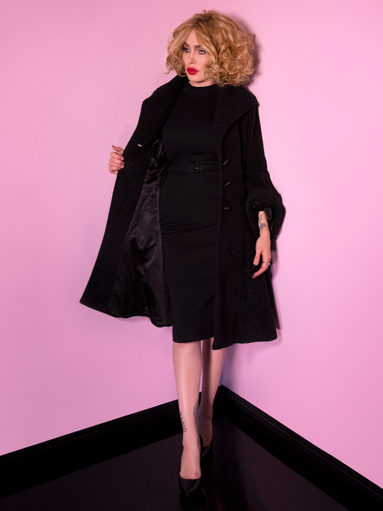 Micheline Pitt covering up the Bad Girl Wiggle Dress in Black with a long coat.
