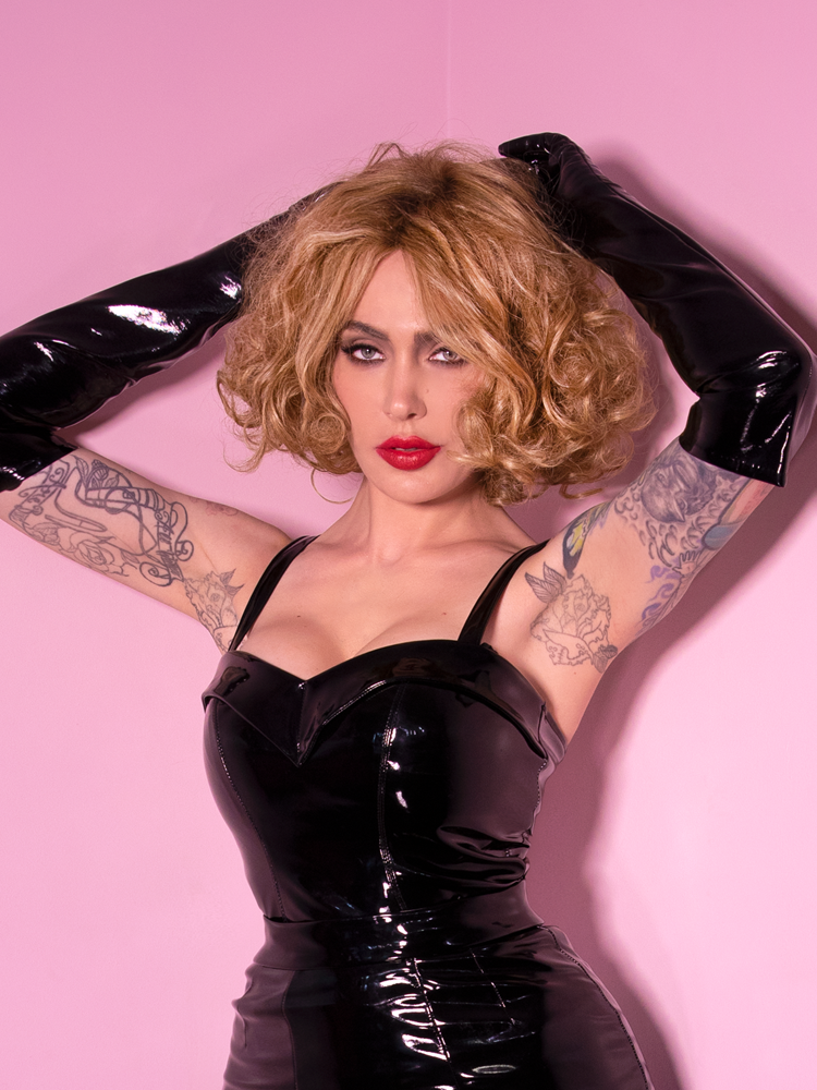 With both arms raised above her head and held slightly behind, Micheline Pitt wears the Miss Kitty Maneater Top in Black Vinyl for Vixen Clothing.