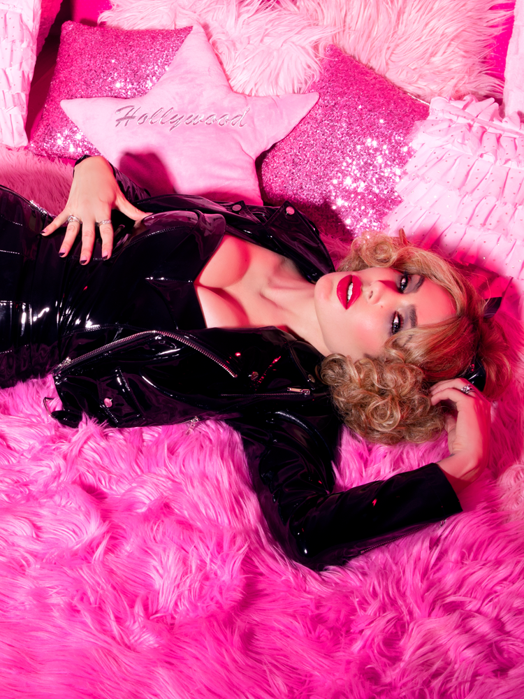 Laying down on a bed of pink pillows and blankets, Micheline Pitt wears the Miss Kitty Maneater Top with matching jacket and bottoms from Vixen Clothing - a vintage inspired clothing brand.