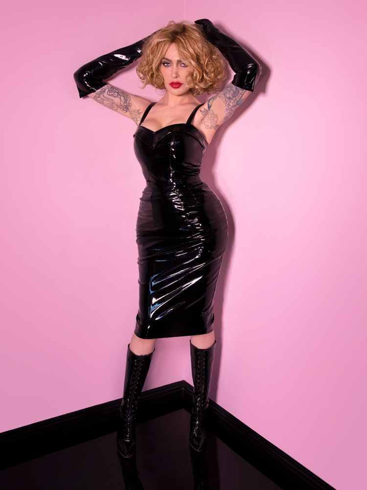 Micheline Pitt wearing the Miss Kitty Pencil Skirt in Black Vinyl with her arm outstretched over her head and standing against a pink background.
