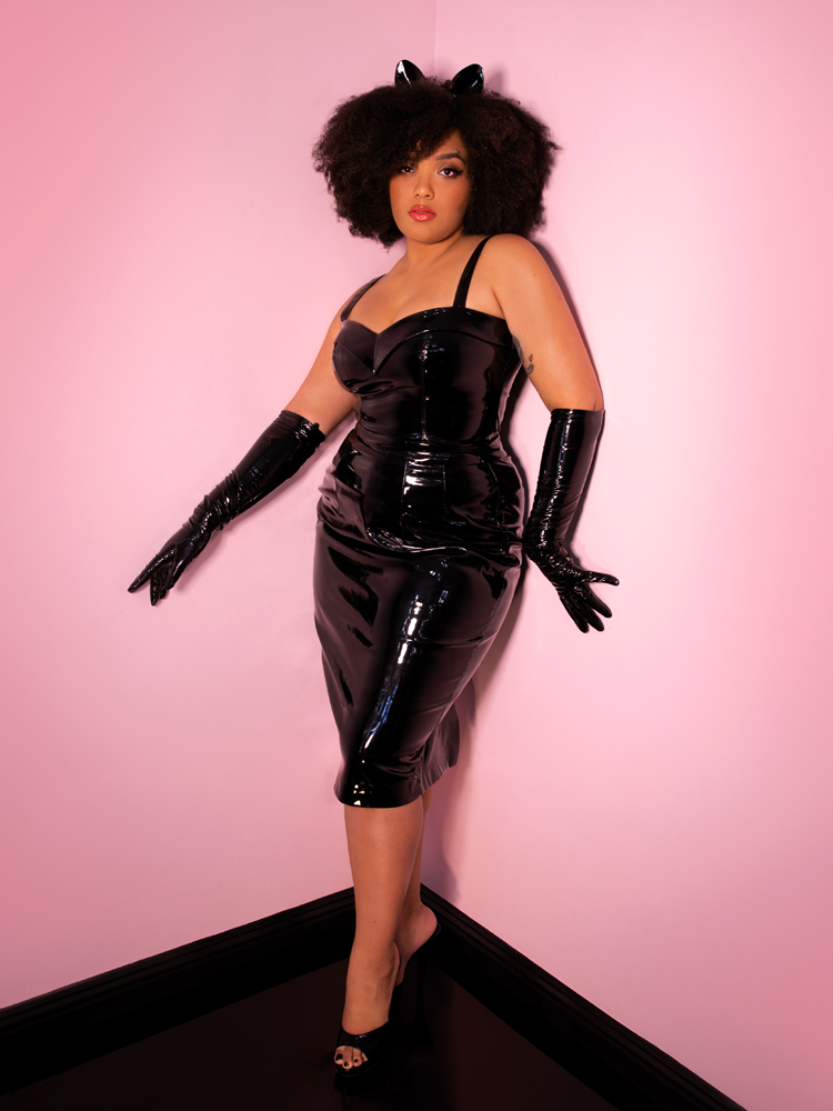 A full length photo of Ashleeta wearing all vinyl, including the Miss Kitty pencil skirt by Vixen Clothing.