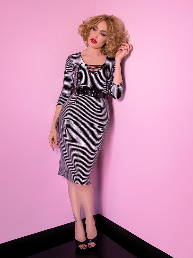 A full shot of Micheline Pitt looking off camera modeling the Vixen Clothing Miss Kitty wiggle dress in black stripes.
