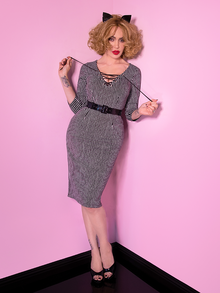 A full shot of Micheline Pitt modeling the Vixen Clothing Miss Kitty wiggle dress in black stripes paired with a kitty ear headband.