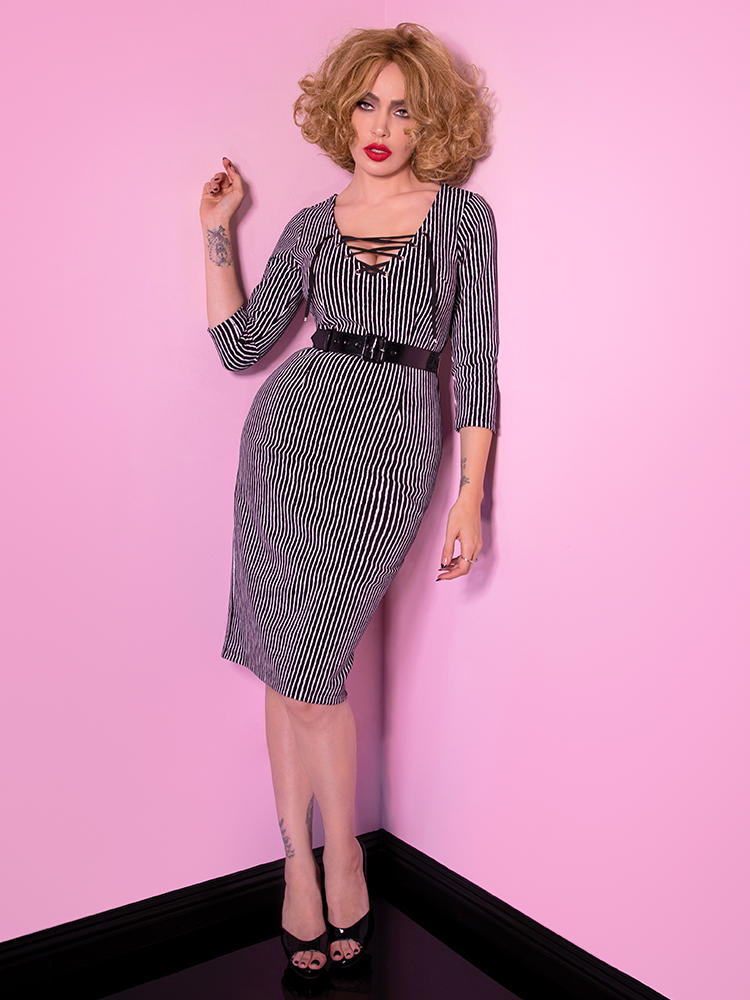 A full shot of Micheline Pitt modeling the Vixen Clothing Miss Kitty wiggle dress in black stripes.