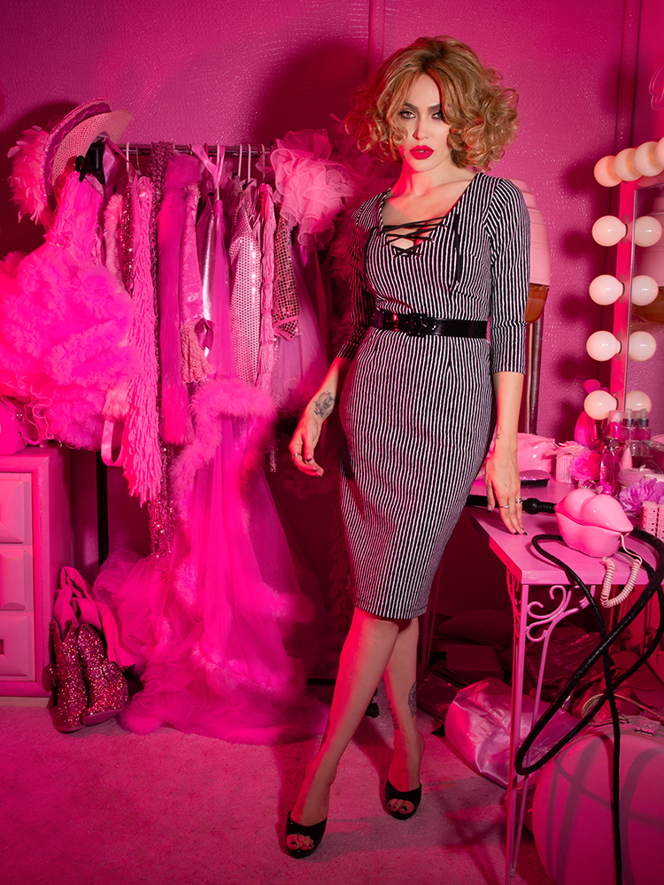 A stylized photo of Micheline Pitt looking at the camera in a pink dressing room modeling the Vixen Clothing Miss Kitty wiggle dress in black stripes.