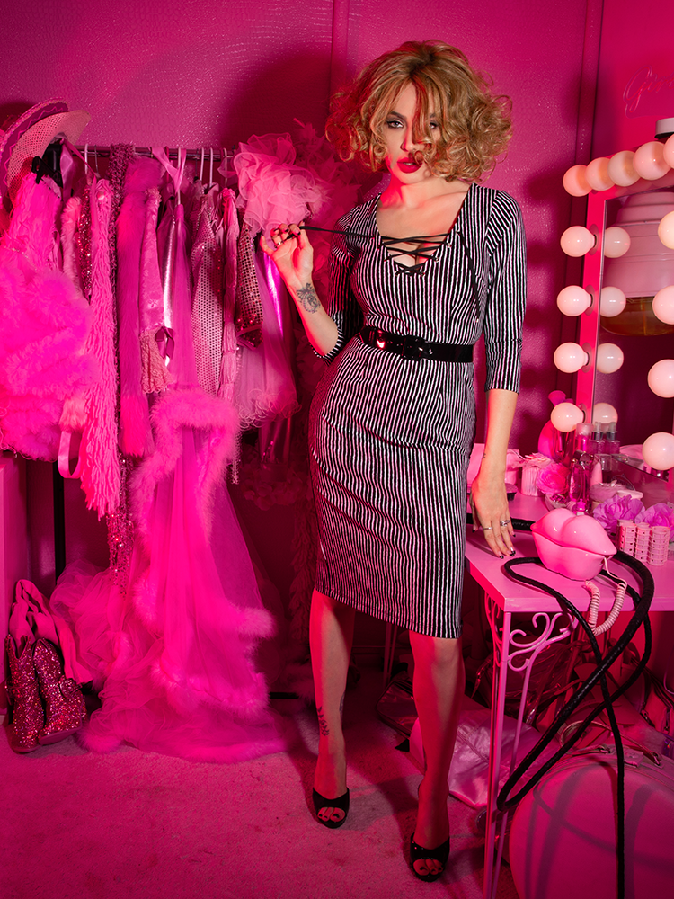 A stylized photo of Micheline Pitt in a pink dressing room looking at the camera modeling the Vixen Clothing Miss Kitty wiggle dress in black stripes.