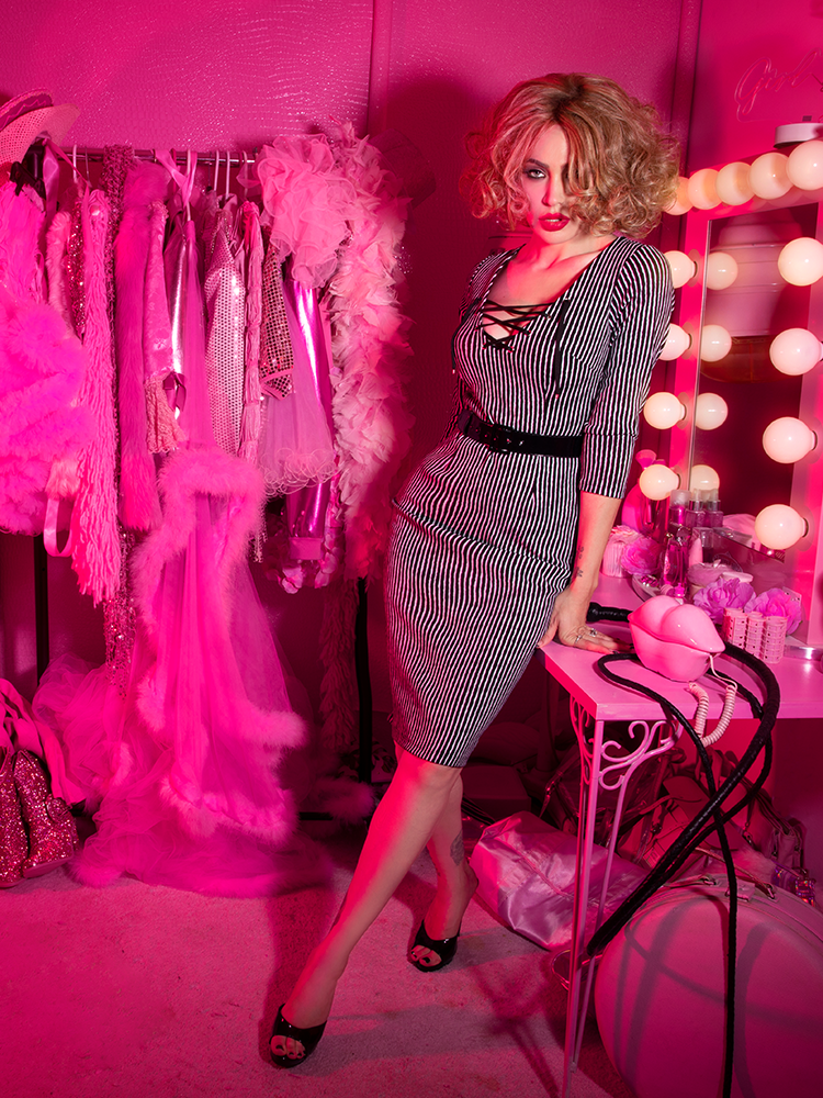 A stylized photo of Micheline Pitt in a pink dressing room modeling the Vixen Clothing Miss Kitty wiggle dress in black stripes.