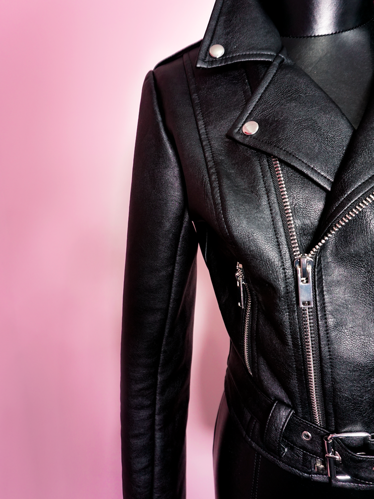 Close-up product shot of the intricate stitching and zipper craftsmanship on the Bad Girl Cropped Motorcycle Jacket in Vegan Leather.