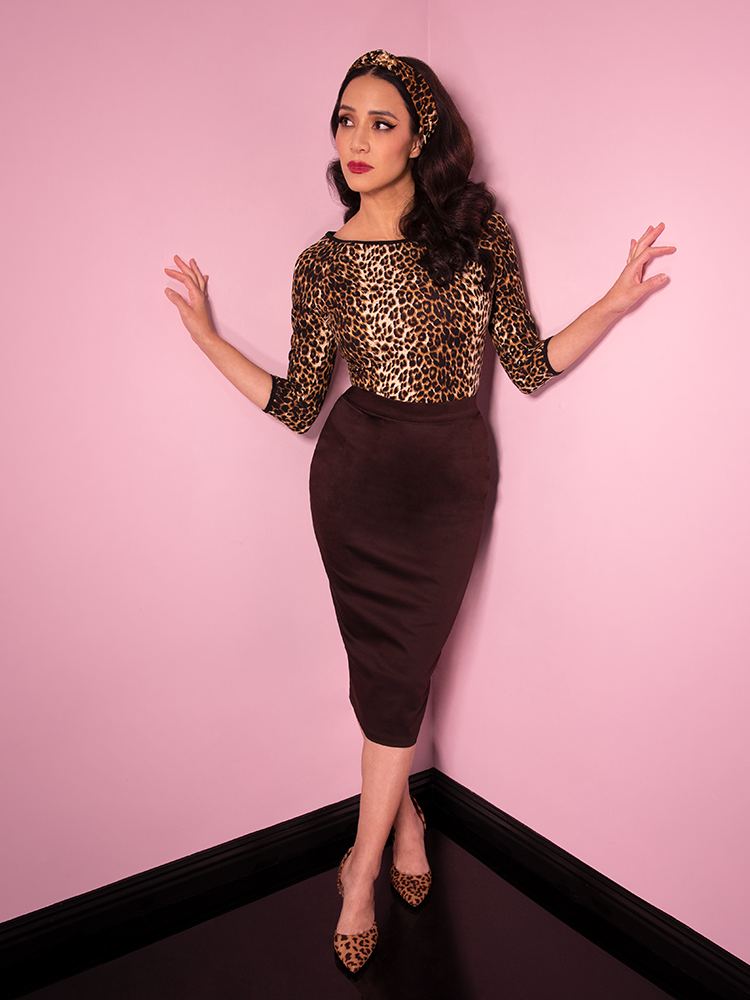With her arms outstretched and placed against the walls, Milynn Moon wears the retro inspired outfit from Vixen Clothing - a chocolate brown pencil skirt along with leopard print top and headband.