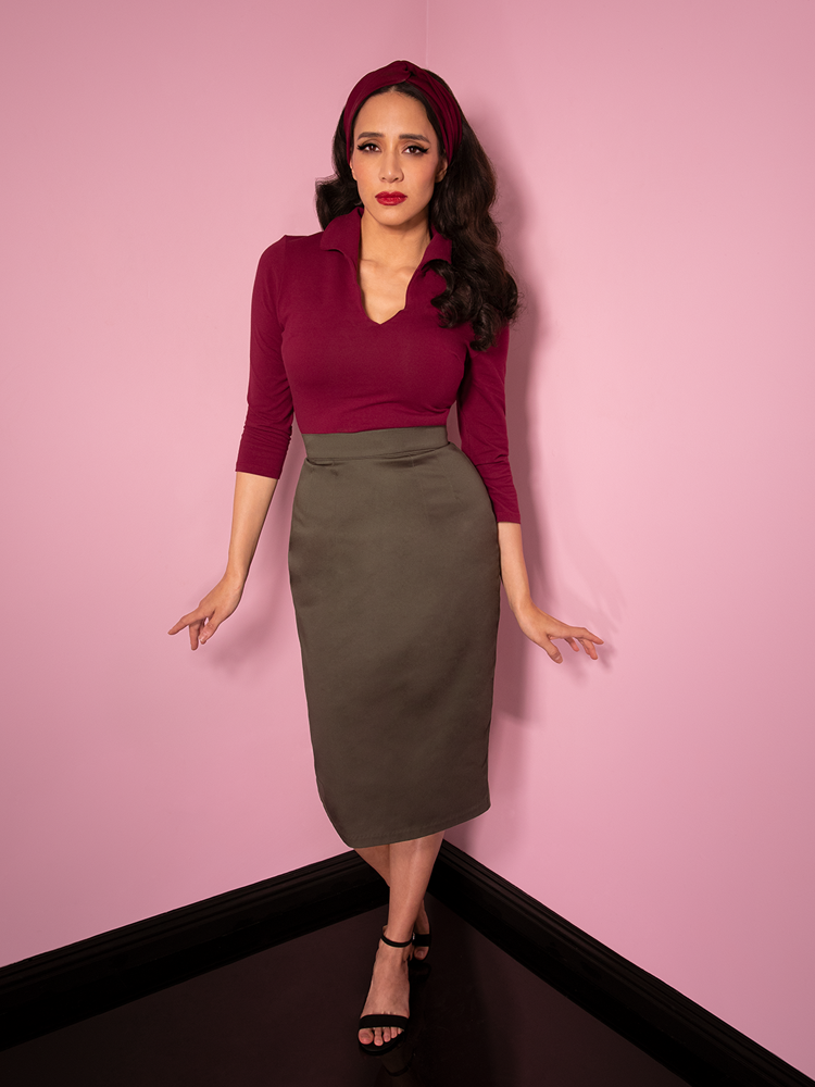 Milynn Moon wearing a retro inspired outfit from Vixen Clothing featuring a Pencil Skirt in Dark Sage along with long sleeve maroon top.