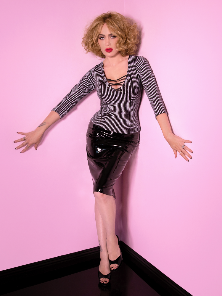 Arms stretched out and hands pressed against pink walls, Micheline Pitt stares directly into the camera while wearing a Vixen Clothing outfit featuring black and white striped shirt with black vinyl skirt.