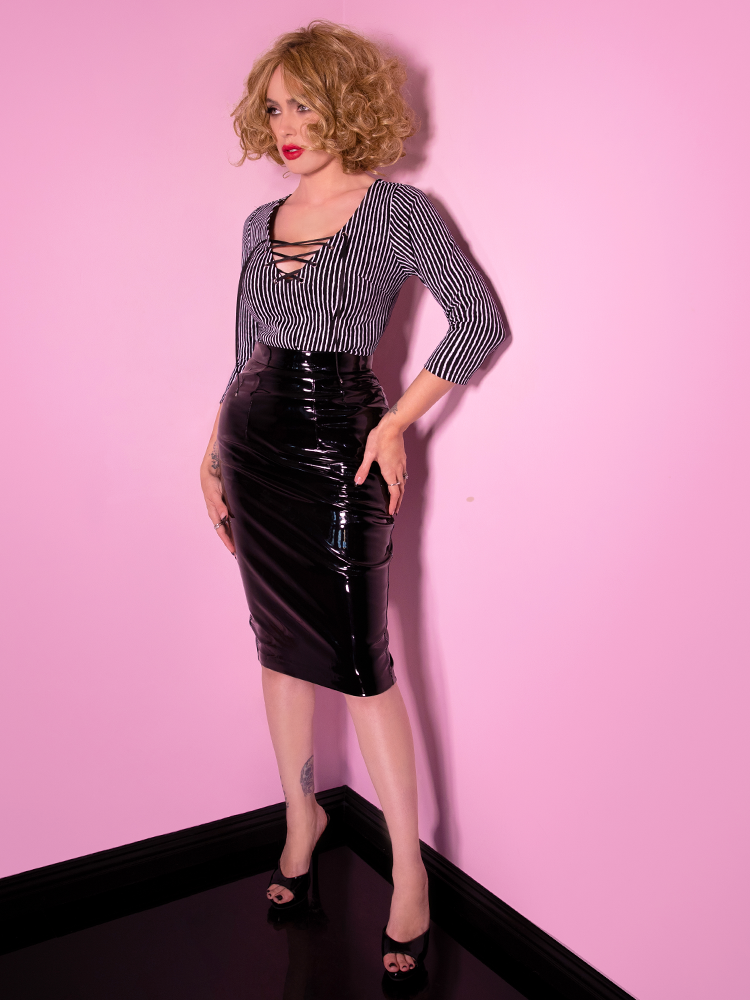Full length body shot of Micheline Pitt wearing a retro inspired black vinyl skirt, black and white striped shirt with string tie and blonde messy hair.