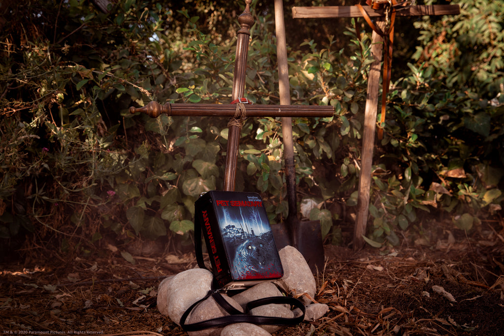 Pet Sematary book purse staged in a makeshift pet burial scene with large stones and wooden crosses.
