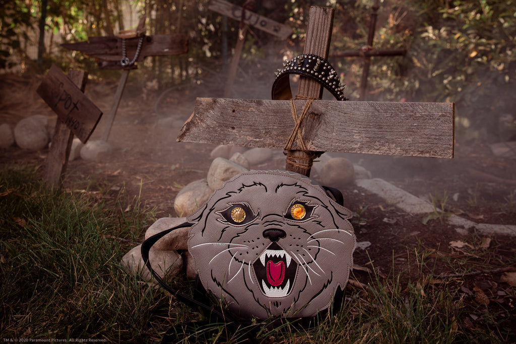 Close-up shot of Pet Sematary cat body bag placed against two pieces of old wood made into a makeshift cross.