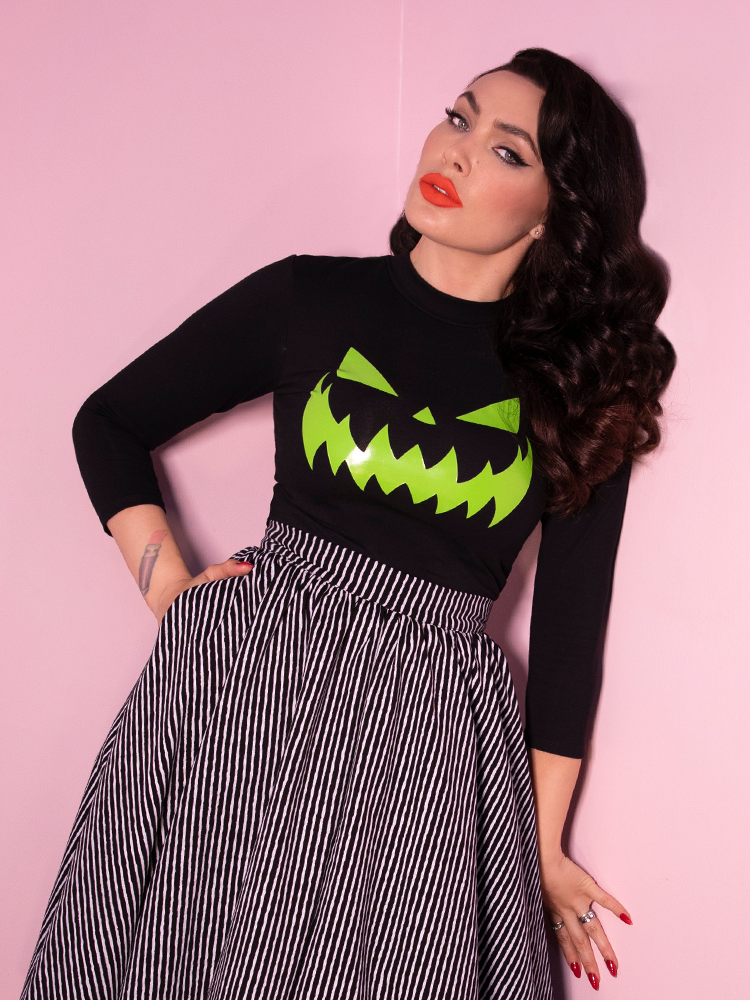 Standing and slightly leaning against a pink wall, Micheline Pitt models a retro style top featuring glow in the dark jack-o-lantern artwork that has been screen-printed on the front.