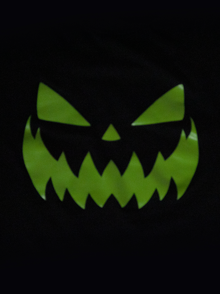 Close-up shot of the jack-o-lantern print of the shirt glowing in the dark.