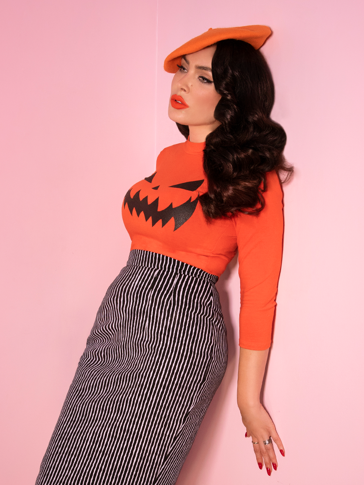 With her shoulders leaning into a wall, Micheline Pitt wears the most recent Halloween release from Vixen Clothing. An orange, 3/4 sleeve top with a classically designed pumpkin face screen-printed on the front.