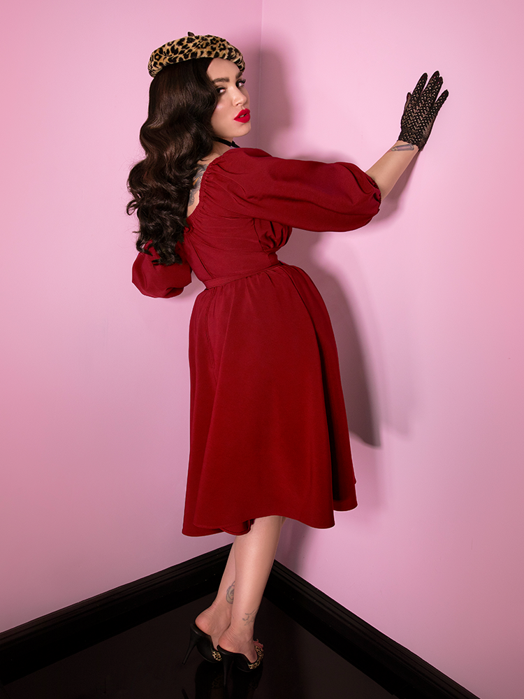 Back shot of Micheline Pitt wearing the Vacation Dress in Ruby Red with a leopard beret and black gloves.