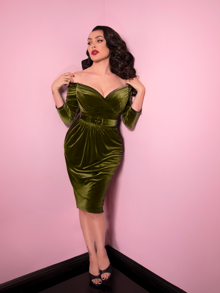 Full body shot of Micheline Pitt posing against pink walls while wearing the brilliant Olive Green Starlet Wiggle Dress from Vixen Clothing.