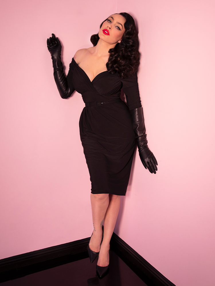 Full body picture of Micheline Pitt wearing a black vintage style dress and black faux leather gloves.
