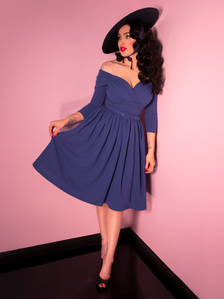 Micheline Pitt looking off camera and holding her skirt modeling the Starlet swing dress in stormy blue paired with a black straw sunhat.