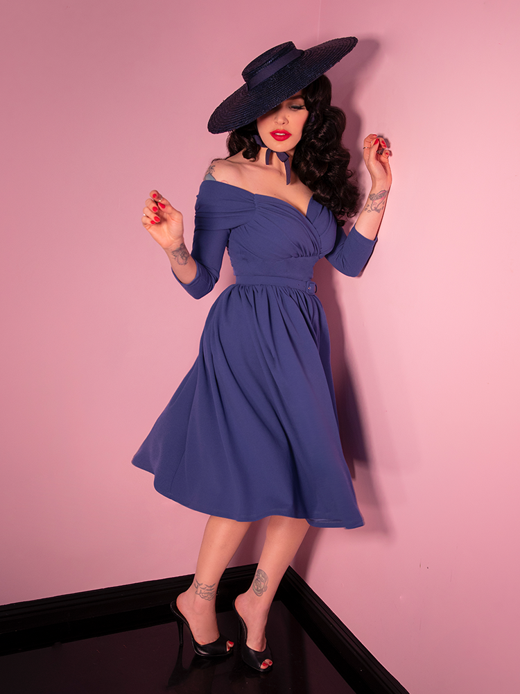 Micheline Pitt twirling in the Starlet swing dress in stormy blue paired with a black straw sunhat.