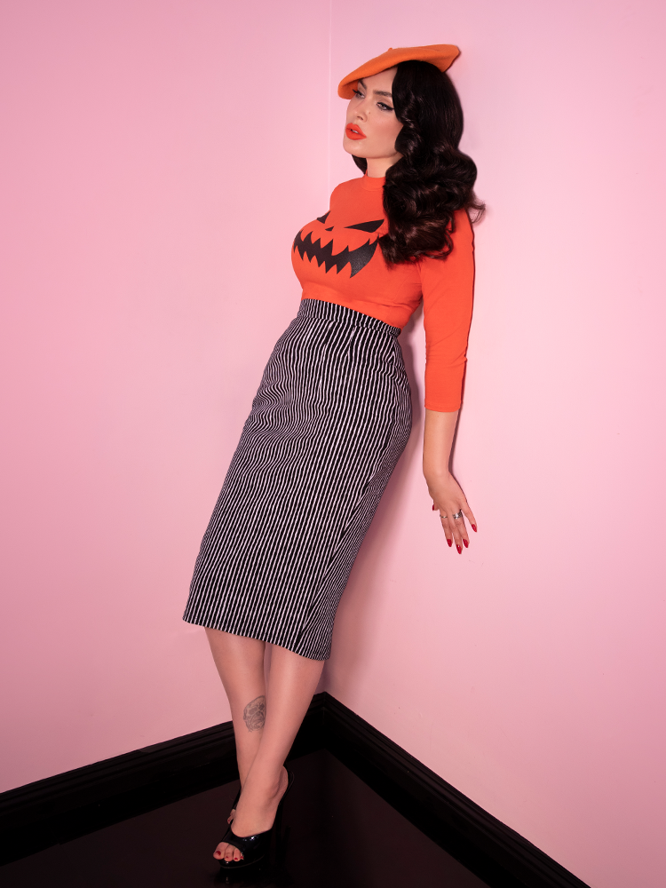 Micheline Pitt leaning against a wall while modeling the Vixen Pencil Skirt in Black and White Stripes from Vixen Clothing.