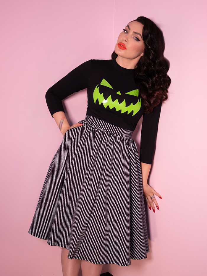 Leaning to her left, Micheline Pitt sports a green jack-o-latern black top along with the newest retro inspired skirt from Vixen Clothing.