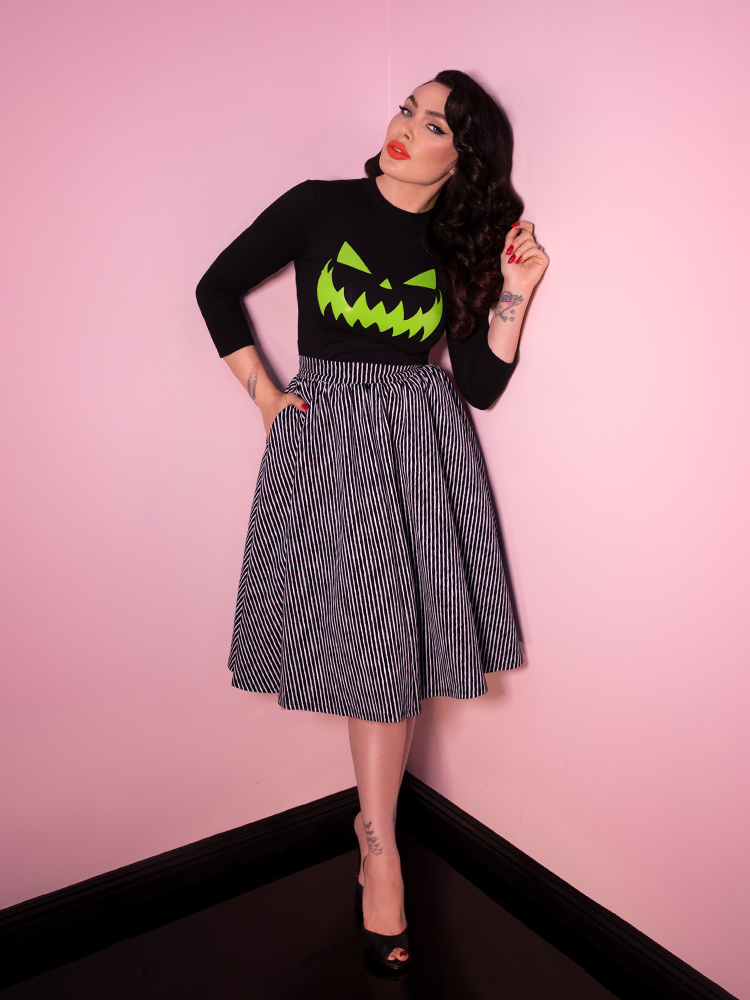 Black haired model wearing the Vixen Swing Skirt in Black and White Vertical Stripes. To get herself fully into the Halloween spirit, she's also wearing a black long sleeve top with a green jack-o-lantern face.