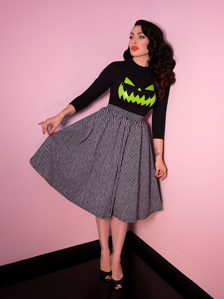 Pinching and pulling the fabric of her new Swing Skirt in Black & White Stripe, Micheline Pitt gets ready for the Halloween season with this newest retro style clothing item.
