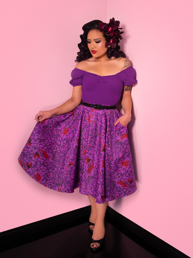 Vixen model Janny in an all purple retro outfit featuring the Vixen Circle Skirt in Sea Siren Print.