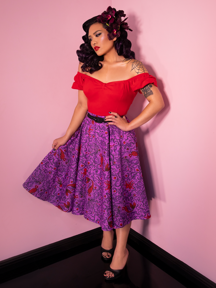 Janny wearing a vintage inspired outfit - off the shoulder red top and purple novelty print skirt.