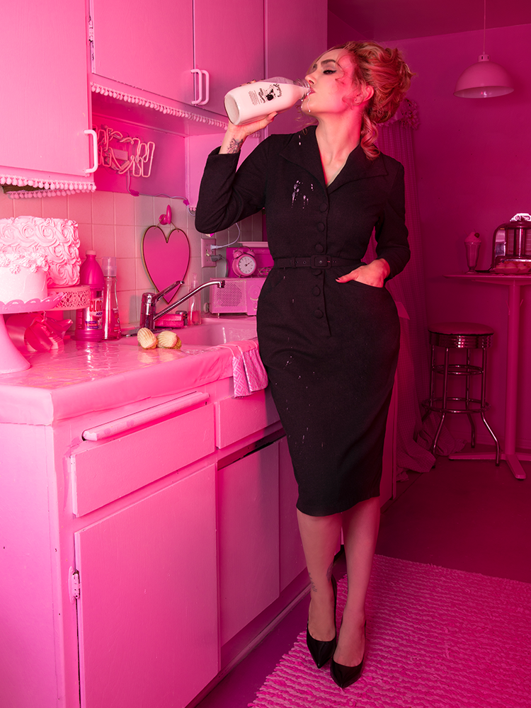 A stylized photo of Micheline Pitt drinking milk in a pink apartment wearing the Vixen Clothing Miss Kitty Secretary dress in dark grey.