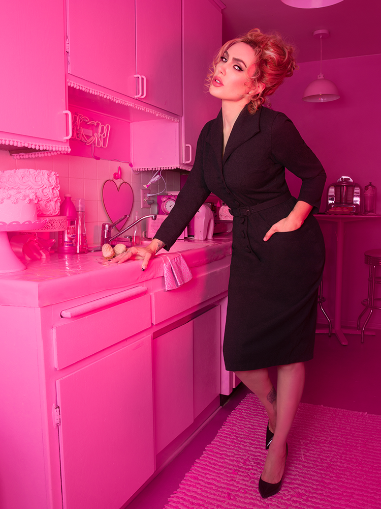 A stylized photo of Micheline Pitt in a pink apartment leaning onto a counter wearing the Vixen Clothing Miss Kitty Secretary dress in dark grey.