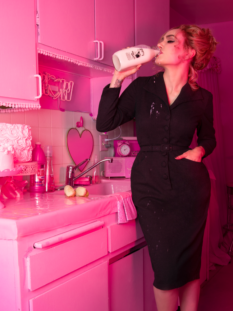 A closeup stylized photo of Micheline Pitt drinking milk in a pink kitchen wearing the Vixen Clothing Miss Kitty Secretary dress in dark grey.