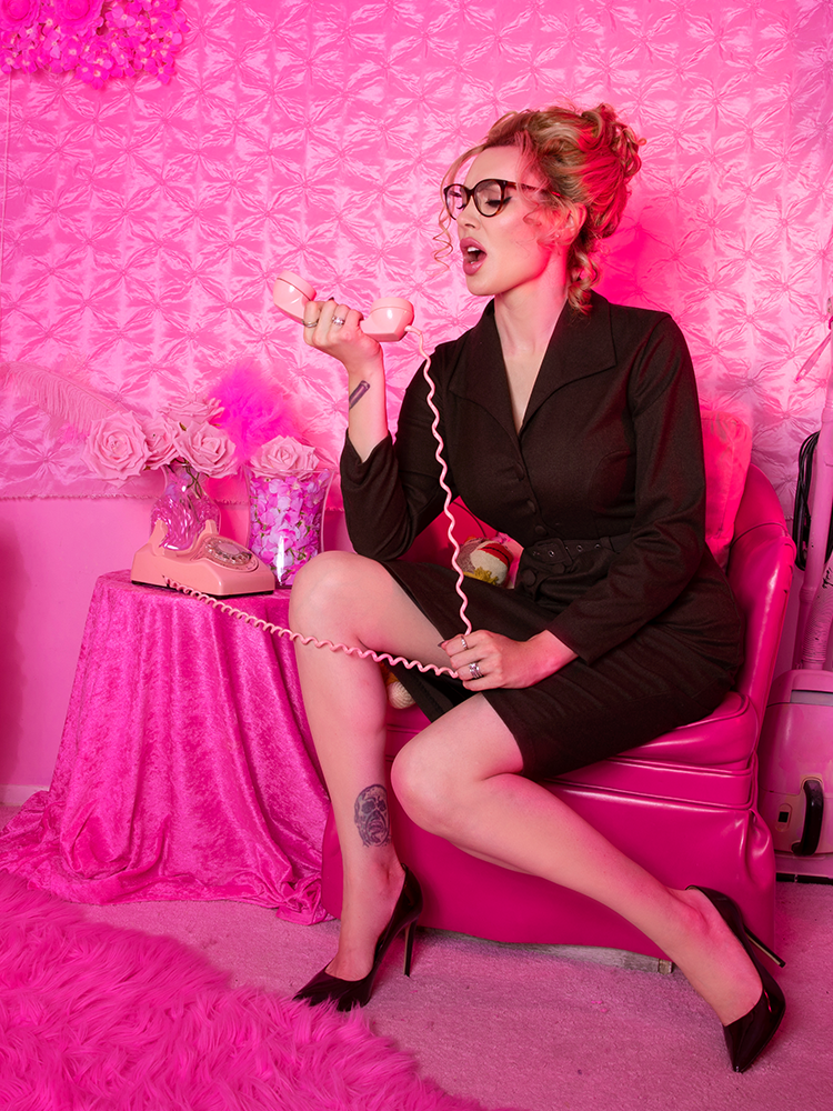 Micheline Pitt sitting on a vinyl hot pink chair yelling into a rotary phone while wearing the Miss Kitty Secretary Dress in Brown.